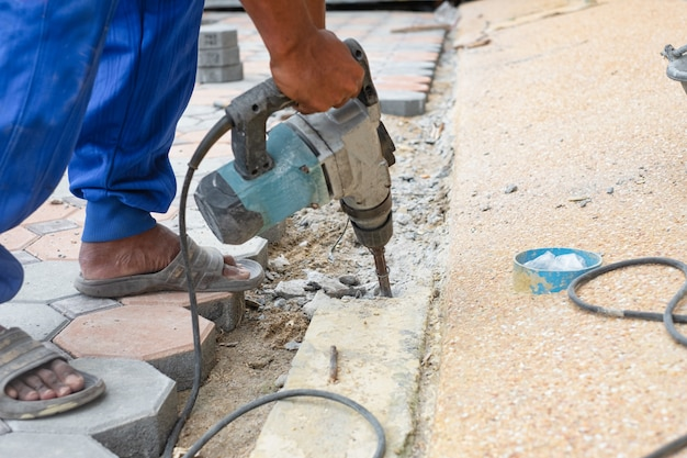 Construction work drilling cement concrete on footpath using electric mortar drilling machine. construction work concept.