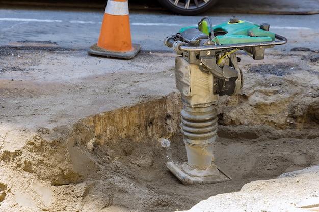 Строительные работы на тротуаре, установка электроинструмента вибромолота на землю при строительстве