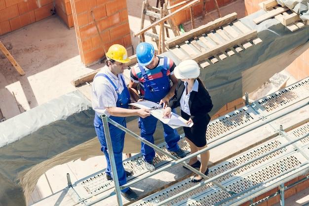 建設作業員と建築家が建築現場の計画について話し合う