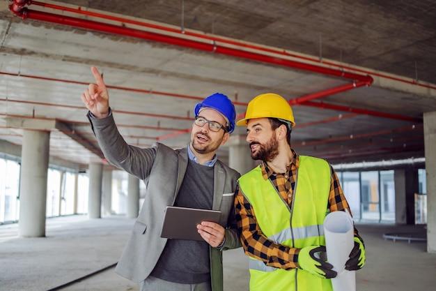 建設作業中の建物に立ち、プロジェクトについて話し合う建設労働者と建築家。何かを指している建築家。