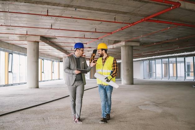 建設作業員と建築家が建設過程で建物の中を歩き、プロジェクトについて話し合っています。
