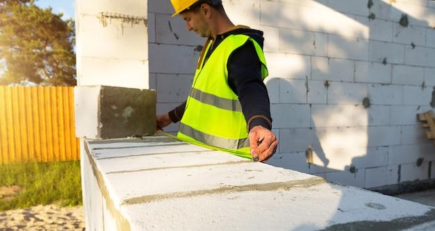 建設現場の建設作業員は、窓の開口部と壁の長さを巻尺で測定します。コテージは、ポーラスコンクリートブロック、保護服-ヘルメットとベストで作られています