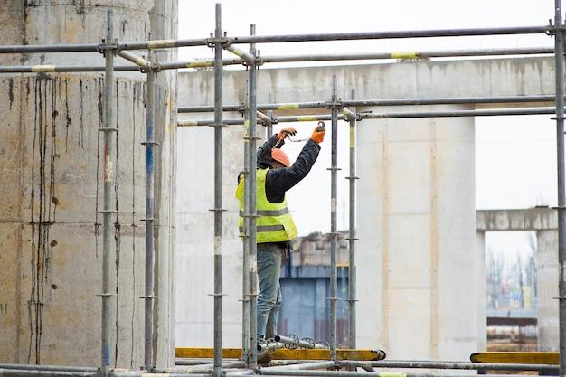 건설 노동자는 건설 지역의 비계에 안전 로프로 자신을 연결합니다