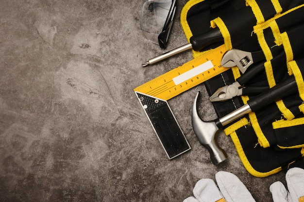 Construction worker belt with tools on concrete texture background. free space for text