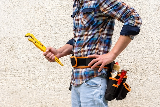 A construction worker in a blue checked shirt with tools in his belt holds a yellow wrench in his hands.
