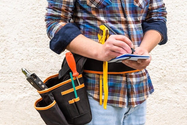 A construction worker in a blue checked shirt with tools in his belt makes a note with a pencil in a notebook.