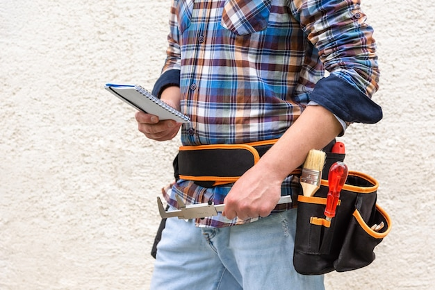 A construction worker in a blue checked shirt with tools in his belt. the worker holds a notepad and a measuring tool in his hand.