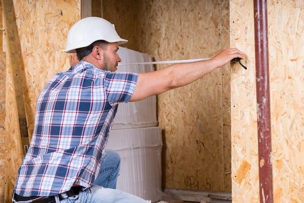 미완성된 집에서 측정 테이프로 문틀의 폭을 측정하는 흰색 안전모를 쓴 건설 노동자 빌더