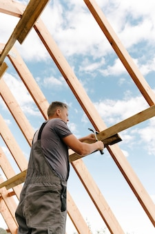Construction worker building the roof of the house