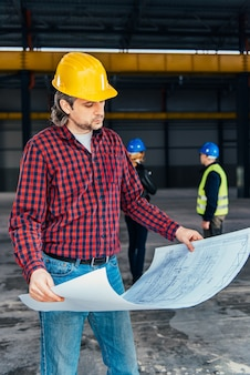 Construction worker checking blue prints