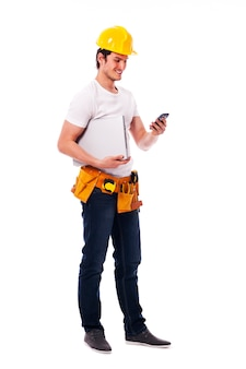 Строитель что-то проверяет по мобильному телефону