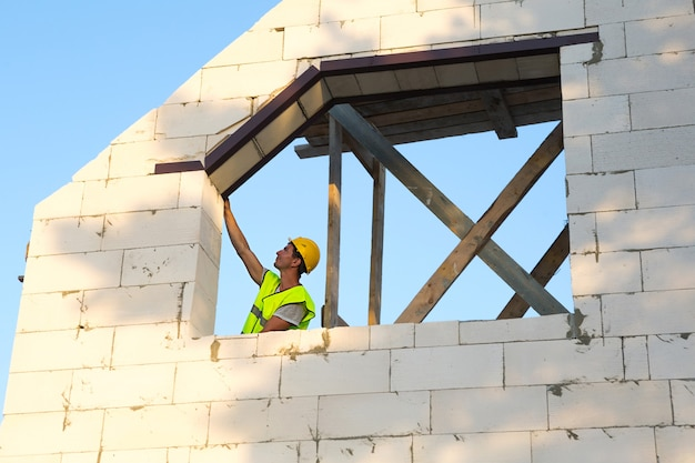 Construction worker at construction site measures the length of the window opening and the wall with tape measure. cottage are made of porous concrete blocks, protective clothing - hardhat and a vest