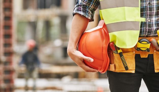 建設労働者は、建設と制服を着て働く男性のプロのビルダーの写真をトリミングしました