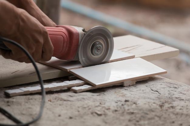 앵글 그라인더를 사용하여 타일을 절단 건설 노동자