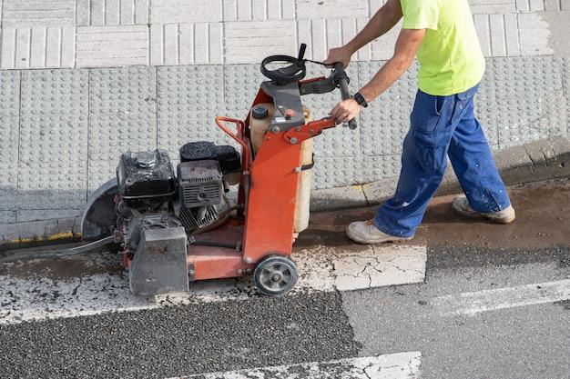 Строитель режет бетонный пол с помощью алмазной пилы на тротуаре