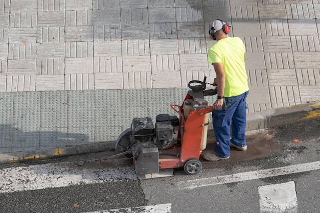 Construction worker cutting concrete floor with diamond saw blade machine on a sidewalk