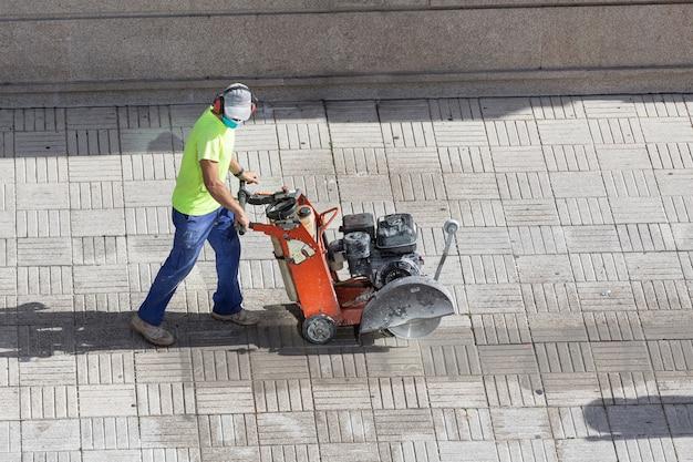 Строитель режет брусчатку пол с алмазной пилой на тротуаре