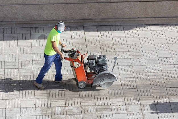 Construction worker cutting paving stone floor with diamond saw blade machine on a sidewalk