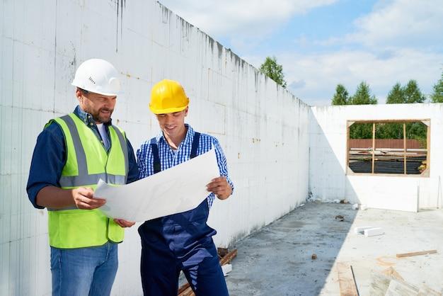 スーパーバイザーとフロアプランについて議論する建設労働者