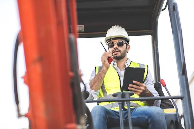 Строитель за рулем экскаватора или обратной лопаты на строительной площадке. молодой латиноамериканец, работающий с тяжелым оборудованием
