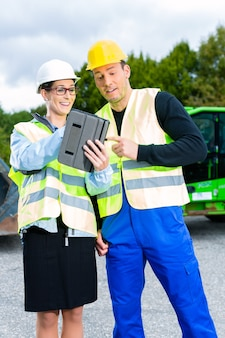 Construction worker and engineer on site discussing blueprints on pad or tablet computer, excavator and other construction machinery