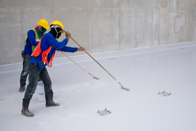 Construction worker epoxy painting at floor for water proof protection