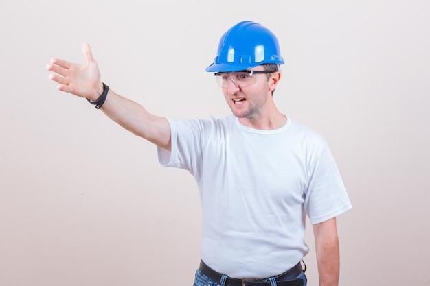 Operaio edile che dà istruzioni in maglietta, jeans, casco e sembra aggressivo