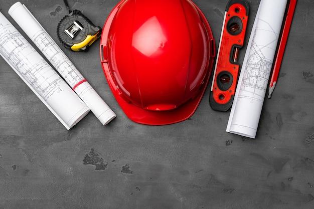 建設労働者のヘルメット、青写真と.constructionレベル、木製の上面図