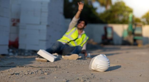Строитель попал в аварию, лежа на полу во время работы на стройке. несчастный случай на работе
