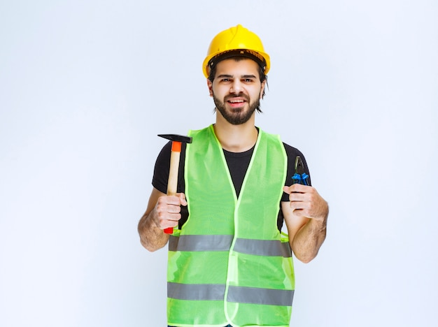 파란색 펜치와 발톱 망치를 손에 들고 있는 건설 노동자.