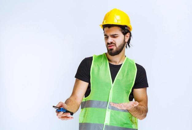 青いペンチを持っている建設作業員は、混乱して不満を持っているように見えます。
