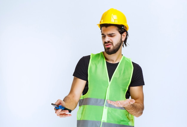 Construction worker holding blue pliers and looks confused and dissatisfied.