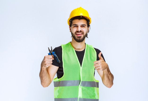 Construction worker holding blue pliers and showing thumb up.