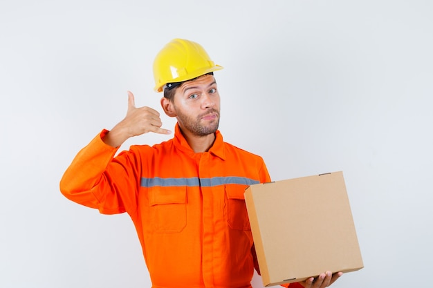 Construction worker holding cardboard box, showing phone gesture in uniform, helmet and looking gentle. front view.