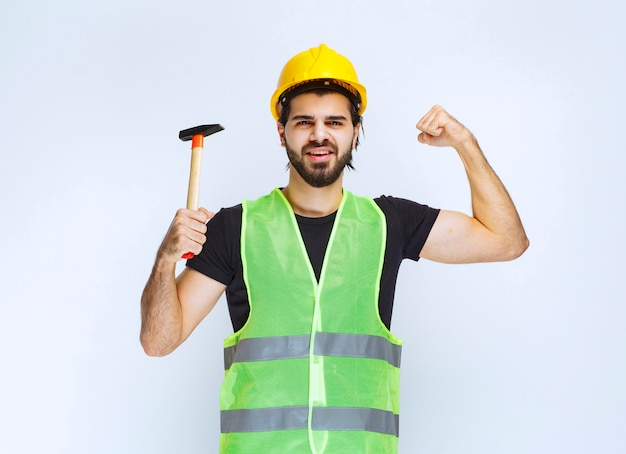 Construction worker holding a claw hammer and feeling powerful.
