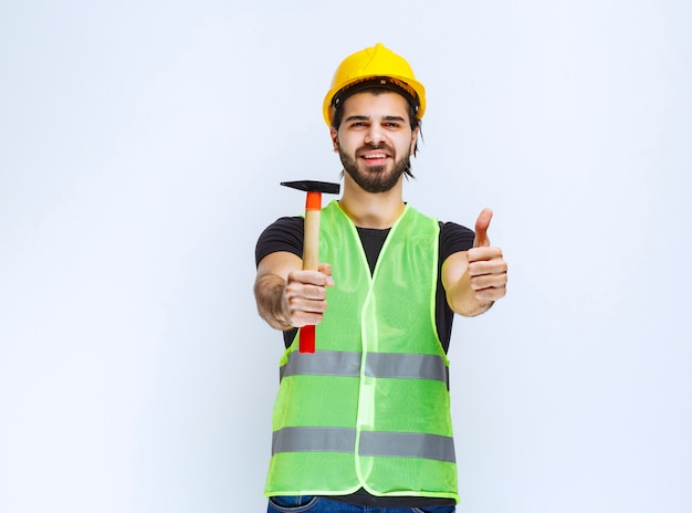Construction worker holding a claw hammer and showing enjoyment sign.