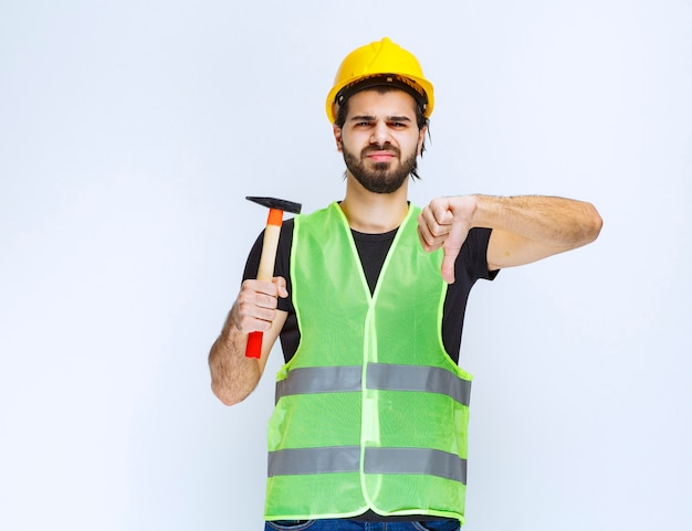 Construction worker holding a claw hammer and showing thumb down sign.