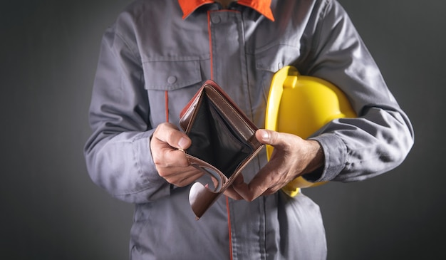 Construction worker holding empty wallet.