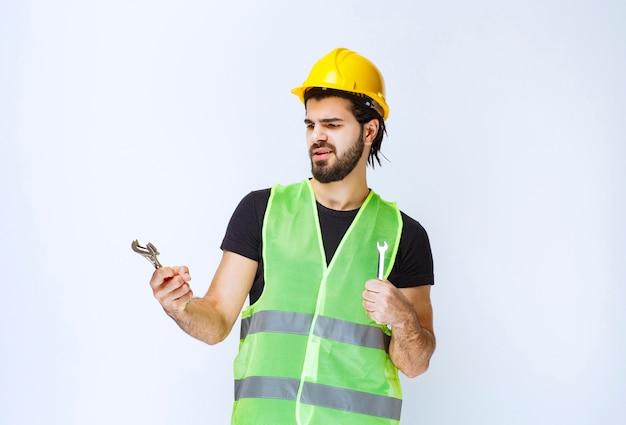 기계 수리를 위해 렌치와 스패너를 들고 있는 건설 노동자.