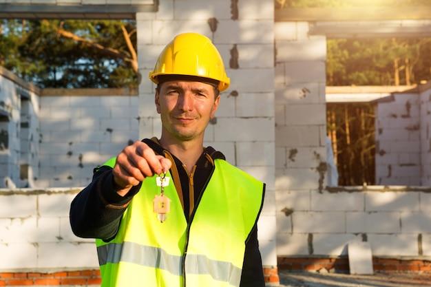 건설 노동자는 집 열쇠를 들고 있습니다. 턴키 건설, 이전, 모기지. 다공성 콘크리트 블록으로 만든 집 벽의 배경에 대한 보호 장비 엔지니어.
