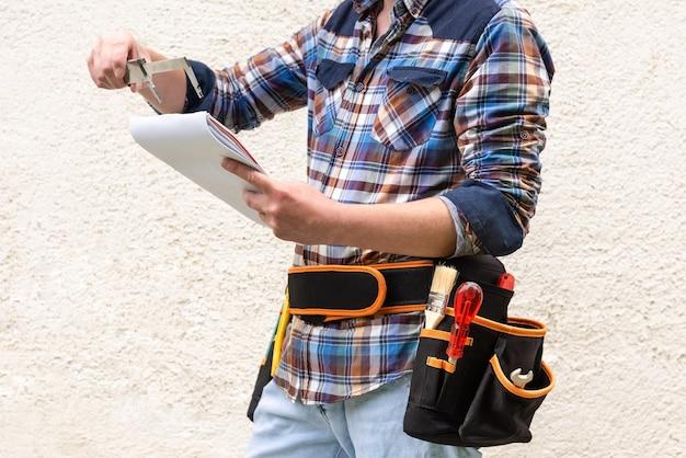 Рабочий-строитель в голубой клетчатой рубашке с инструментами в поясе.