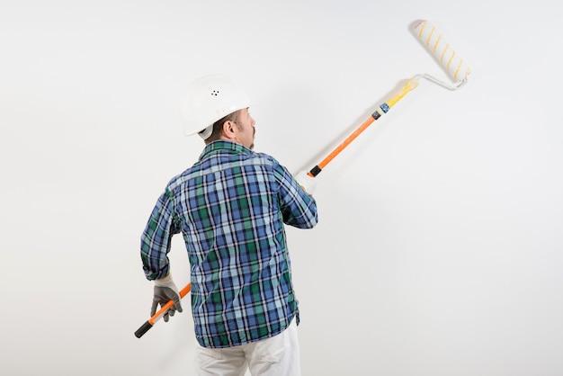 하드 모자에 건설 노동자 긴 롤러와 흰 벽 페인트