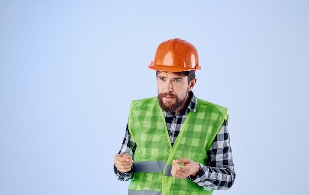 파란색 배경과 격자 무늬 셔츠 반사 조끼에 주황색 하드 모자에 건설 노동자