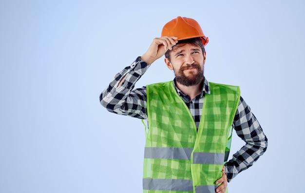 파란색 벽과 격자 무늬 셔츠 반사 조끼에 주황색 하드 모자에 건설 노동자