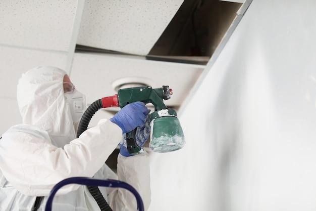 스프레이 건으로 보호 복 및 인공 호흡기 페인팅 벽에 건설 노동자