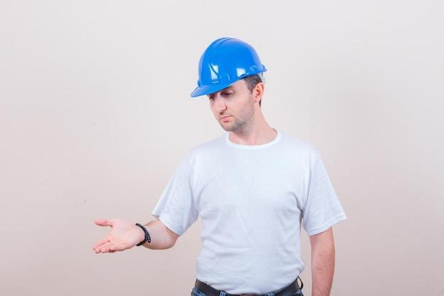 Tシャツ、ジーンズ、ヘルメットの建設労働者が手のひらを疑わしく保ち、真剣に見える