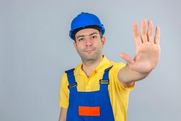 손으로 균일하고 파란색 안전 헬멧 만들기 중지 제스처에 건설 노동자 흰색으로 격리