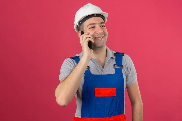 ピンクに分離された携帯電話で話す顔に笑顔で制服と安全ヘルメットの建設労働者
