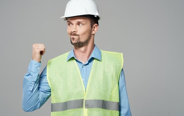 흰색 헬멧과 녹색 반사 조끼에 건설 노동자.