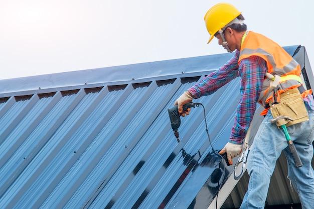 建設労働者は、新しい屋根、屋根用具、金属板を備えた新しい屋根で使用される電気ドリルを取り付けます。
